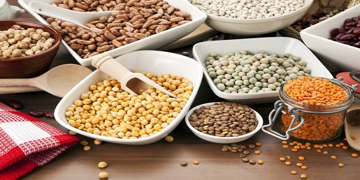 variety of legumes in bowls and glasses, arranged on kitchen table