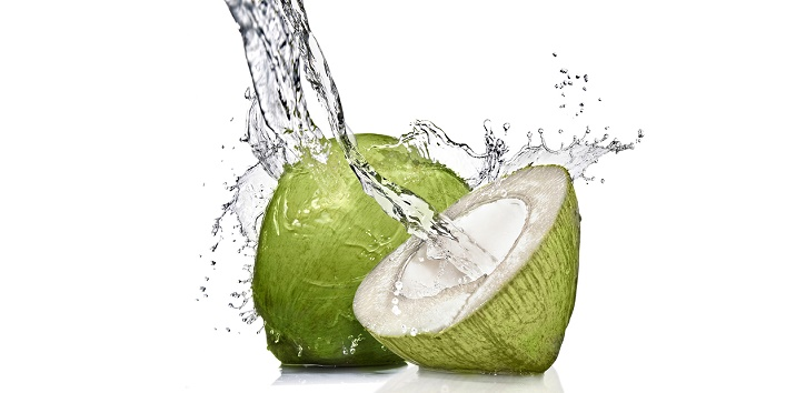 splash of water on green coconut isolated on white